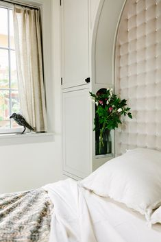 Cubbyholes for nightlights and flowers were built into the cabinetry surrounding the velvet headboard in the master bedroom. The bird sculpture is by Mark Chatterley.