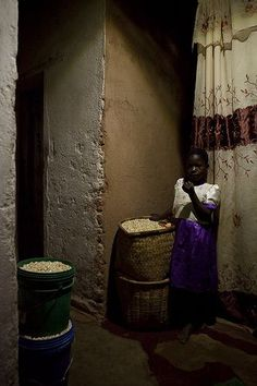 Solar At Home, a young girl next to baskets of corn at home, lit by a solar lamp, Malawi