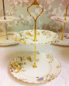 Beautiful yellow poppies and other flowers have been lovingly hand painted onto this pretty cake stand.  Both pieces have a swirling fluted rim with a gently scalloped edge.  The china used was made in England in the 1920s by Aynsley.  The condition is very good with no chips, cracks or crazing,  There is some light rubbing to the gilt  Dimensions are, bottom plate 18.3cm, top 14.5cm, height 24cm.  Box 30   Back to store www.etsy.com/shop/LavenderRoseCottage.
