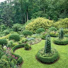 Bursts of colorful flowers, including purple coneflower, violet cranesbill, blue catmint, and white and lavender phlox, punctuate the boxwood hedges and sculptural obelisks.