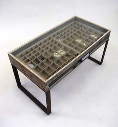 A glass top coffee table, created from an original printers tray.  The printers tray forms the drawer of this table along with its original handle. The per