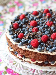 chocolate cream cake with fresh blueberries, raspberries, and chocolate shavings....