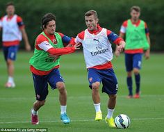 Hands on: Tomas Rosicky tries to stop Jack Wilshere from breaking past him...