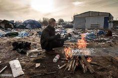 11-20 Hemn, a Kurd migrant, keeps warm next to a fire on a... #calais: 11-20 Hemn, a Kurd migrant, keeps warm next to a fire on a… #calais