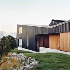 "The home is mostly clad in black trapezoidal-profile steel, with cedar boards lining what the owners call the ""human spaces""—external passages between buildings. A solar hot water system perches on the roof."