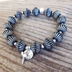 A stretchy bracelet set featuring black & silver Czech glass beads, a logo charm, & shark tooth. All silver is solid sterling silver. This bracelet