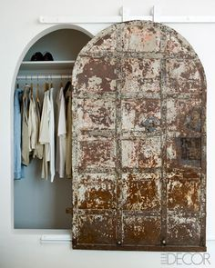 In a guest bedroom, an antique French cellar door is mounted on a custom-made track.