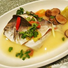 Steamed pomfret prepared Teochew style fish with salted vegetables and salted plums. A signature fish at Chui Huay Lim Teochew Cuisine restaurant in Singapore. Simple with a semi spicy and tangy broth. Chinese Food, Singapore, Seafood, Spicy, Restaurant, Fish, Vegetables, Simple, Ethnic Recipes