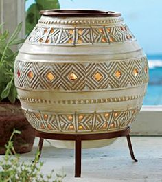 "GLOBAL INSPIRATIONS™ HURRICANE Was $75 Now $30 While Supplies Last  Detailed with geometric designs, our ceramic hurricane captures the spirit of traditional African pottery. A raised metal stand adds to the intrigue. Add a votive or tealight, sold separately, to the metal candle hanger's glass votive cup. 10½""h, 9""dia.  http://www.partylite.biz/legacy/sites/stevengerard/productcatalog?page=productdetail&sku=P90971&categoryId=55268&showCrumbs=true"