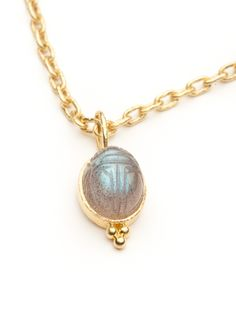 This unique charm is composed of a cabochon labradorite with engravings that resemble an Egyptian scarab.  The stone is bezel-set in 19kt hand-hammered yellow gold and has granulation details.  The bale does not open but has a wide opening of a 0.25 of an inch.  It measures 1.25 inches from top to bottom and 0.5 inch across.