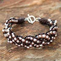 This handmade creation is offered in partnership with NOVICA, in association with National Geographic. Knotted by hand, three strands of radiant pink pearls encircle the wrist in this unique bracelet.