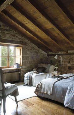 00310506. Dormitorio de invitados en tonos fríos con paredes de piedra y vigas de madera_00310506