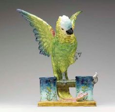 A french majolica model of a parrot and mouse, black painted mark for Delphin Massier, Vallauris, (a.m.), circa 1880. Naturalistically modelled with wings spread, the large animated exotic bird raising one claw from his perch while spying a small mouse at the rim of one of the supporting cylindrical vases, on a rectangular faux bois base. 21 in. (53.3 cm.) High.