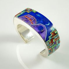 Inlaid Bracelet by Bryon Yellowhorse. Sterling silver hand-fabricated inlaid Navajo bracelet with sugilite, lapis, turquoise, red and pink coral, jet and spiny oyster shell by Navajo artist Bryon Yellowhorse. The focal point incorporates mountains and the night sky with a crescent moon and shooting star. Bright inlaid geometric patterns fall to either side.
