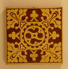 Earthenware tile, dust-pressed red body inlaid with buff with worn clear glaze, feturing a central circle with Gothic tracery and four zoomorphic foliate motifs at the corners.  Makers mark on reverse.