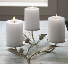 This silvery sprig sprouts delicately ribbed leaves and textural berries along with three platform discs to hold pillar candles. Finely detailed and crafted of iron, this graceful candelabra makes a stunning centerpiece for the holiday table.