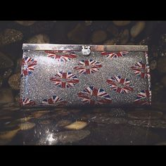 Union Jack Wallet Smooth, sparkly wallet with a snatch that makes it easy to open and close. Union Jack lips placed all over the wallet really give it a pop of color! Inside there is a black interior with different pockets to hold your cards, money, change, etc. I've had it for quite a while but it looks new! Bags Wallets