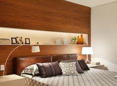 No quarto do morador, o painel de madeira faz as vezes de cabeceira com nicho para objetos de décor e porta-retratos (Foto: MCA Estúdio)