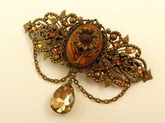 Diese sommerliche Haarspange mit Blume setzt echte Highlights. Sie besteht aus bronzefarbenem Metall. Auf der Rückseite befindet sich eine