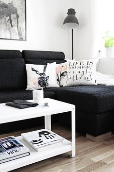 Love this living room with black couch and white accent pillows and coffee table