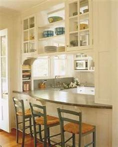 Pass through window over bar with shelving and two sided doors. Love this!