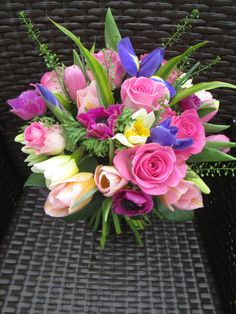 Spring bouquet of iris, aqua pink rose, daffodil, anemone, tulip and thalspi. Spring wedding flowers