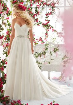 This soft net Mori Lee 6812 wedding dress creates an A-line silhouette and has an asymmetrically pleated, surplice bodice with sweetheart neckline. This sleeveless gown features spaghetti straps spanning the shoulders and a semi-open, V-cut back, accented with covered buttons. A detachable satin bow belt embellished with crystal beading cinches the waistline. The full skirt is softly gathered and features a chapel train.
