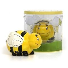 """The Benji Bumblebee Bank is a beautiful hand crafted ceramic bank.  The Bumblebee Bank stands 5.5"""" long and is 3.5"""" high.  Coins and bills can be easily inserted through the coin slot on the top.  It is yellow with black and white details - all hand decorated.  This is one of the cutest coin banks ever and it comes it its own sturdy bug-keeper box with handle. The bug keeper is meant to be used as the real thing, it's even got air holes in the top of the lid!!  The reusable container is…"""
