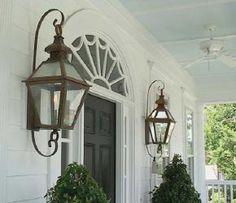 Transom window millwork, gas lanterns, black door, ivy topiaries
