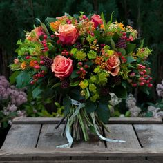 A cheerful bouquet full of sunny 'Cherry Brandy' luxury roses and 'hypericum' red berries. Made by Moyses Stevens florists.