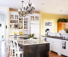Golden yellow was a favorite hue from the family's former residence, so they decided to pair it with this home's black-and-white color scheme. The kitchen was an ideal space for a splash of cheery yellow walls. Cathy stuck with black-and-white countertop accessories, light fixtures, and linens. Even the upper cabinets and kitchen island maintained the black-and-white theme.