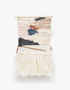 Himara From MINNA, an ultra soft, handwoven wall hanging in multi-tone material with brass dowel. $350  •	Ultra soft small wall hanging •	Brass dowel •	Multi size looms and texture •	Multi layer fringe •	Made with: silky alpaca, roving and cotton •	Made in USA