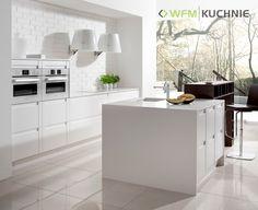 PUREZZA BIAŁY MAT: Klasyczna biel nowoczesnych frontów o ciekawej formie, w których zamiast uchwytu zostało zastosowane wgłębienie na krawędzi, tworzy wrażenie czystości i ponadczasowości. Obszerna wyspa z wbudowanym ciekawym regałem łączy kuchnię z przestrzenią pokoju dziennego. Ekskluzywne szuflady w dolnych szafkach podnoszą funkcjonalność kuchni.