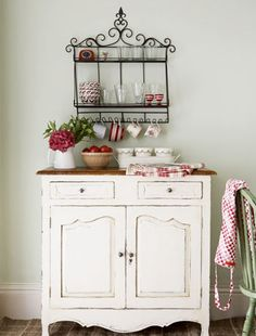 Vintage dresser  Antique metal shelves on the wall transform this dresser into a charming focal point.