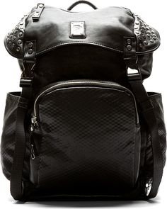 """Diesel Black Mock Leather Studded Rucksack $600 Unstructured mock leather backpack in black. Silver-tone hardware. Flat circular studs. Foldover flap at main compartment with backpack clips & concealed drawstring closure. Textile carry handle at top. Padded adjustable shoulder straps. Logo plaque & zippered welt pocket at front foldover flap. Patch pockets at front & side panels w/ tonal grid texture throughout. Patch pockets inside. Fully lined. Tonal stitching. 14""""L; 15""""H; 8"""" W. 100%…"""