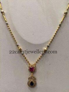 22 carat gold relatively simple gold necklace with crystal round balls and two tone designer pendant. Diamonds, rubies and emeralds studd...