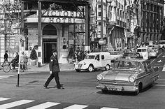Verkeersagent regelt het verkeer voor het Victoria Hotel op de hoek Damrak-Prins Hendrikkade, 1966.