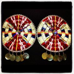 Fine quilled rosette earrings. Porcupine quillwork, used for its beauty or when and where beads are not available, is harder and longer to do. The quills are cleaned, trimmed, flattened, dyed, and inserted into carefully placed holes in the leather backing, sometimes interwoven or sewn on the back of the piece. They take dyes supremely well and look/feel wonderful, but only the most patient artisans practise this art.