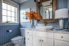Blue bead board walls bring New England charm into the guest bathroom, while a Carrara marble vanity top and accent pieces add a touch of elegance.
