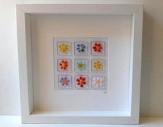 A framed fused glass picture of rainbow coloured flowers. There are 9 glass tiles with a flower fused on each. The box frame measures 25cm x 25cm Made in my home studio Free shipping Thanks for looking
