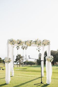 This elegant four poster wedding canopy is draped in light, flowing fabric and adorned with beautiful bouquets of white blooms including hydrangea, chrysanthemum, and touches of lambs ear. {Floral design: Lilypad Florists  // Photography  Marianne Wilson Photography } Click to see more.