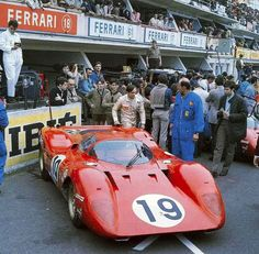 Chris Amon walks round his Ferrari 312P (that he shared with Peter Schetty) at the 1969 24 Heures du Mans next to it, covered by the public, is the 2nd factory 312P, driven by Pedro Rodriguez & David Piperneither of the cars would finish the race Amon already was a Le Mans winner, driving to victory together with Bruce McLaren in 1966 at the wheel of a Shelby American Inc. Ford MkII