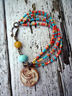 Rustic bird. Cermic beads, ceramic charm. Czech glass seed beads. Mookiate bead. Coral pink, yellow, gold and Turquoise Beads. Vintaj brass.. $32.00, via Etsy.