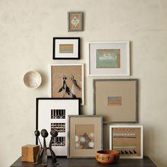 Buscando descontracturar la decoración se optó por una distribución en triángulo, con cuadros en la pared y apoyados al mueble, y con marcos y tamaños diferentes.