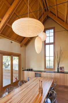Vaulted tongue and groove ceiling, hanging paper pendants.