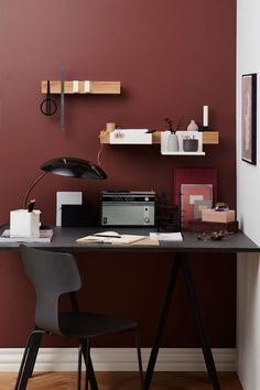 A home office with red walls and a black desk feature the Flex rail by Nordic design brand Gejst.