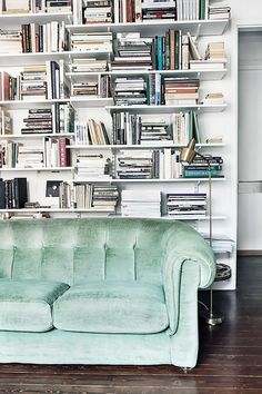 Living room with a wall of bookshelves, and a mint green velvet sofa