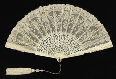Pleated fan, 1885-1890. Leaf of cotton bobbin-made lace backed with silk; sticks of pierced and carved ivory; metal loop at the rivet. Attached tassel. Courtesy of the Cooper-Hewitt National Design Museum.