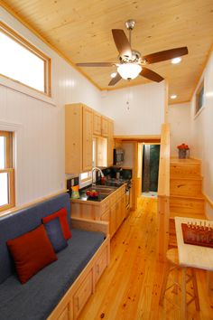 The interior consists of white walls and natural wood flooring, ceiling, and cabinets.