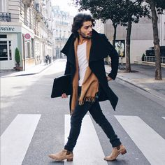 Rock a black overcoat with navy blue slim jeans if you're going for a neat, stylish look. Nude suede chelsea boots will add a touch of polish to an otherwise low-key look.   Shop this look on Lookastic: https://lookastic.com/men/looks/overcoat-crew-neck-t-shirt-skinny-jeans/21277   — Black Overcoat  — Tan Scarf  — White Crew-neck T-shirt  — Black Leather Zip Pouch  — Navy Skinny Jeans  — Beige Suede Chelsea Boots